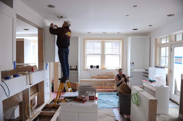 Jess Armitage and Scott McPhie install cabinet lighting and the cabinetry